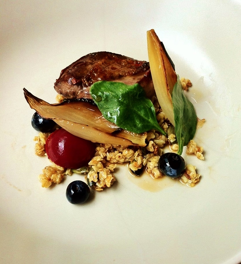 Wild pigeon breast with granola and berries on a white plate
